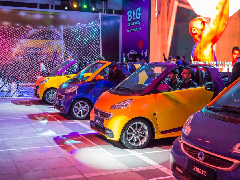 Smart Cars on display outside the arena before the Lakers' exhibition game Tuesday in Beijing. Bryant appears in commercials for the cars on Chinese TV.