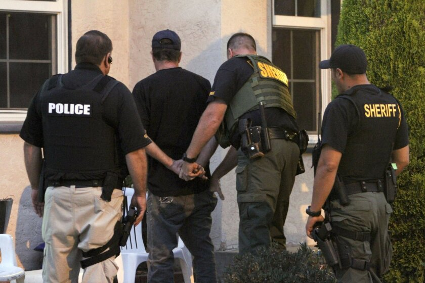 Sheriff's deputies temporarily detain a man as they search his Allied Gardens home as part of a Allied Shield IV, an effort to arrest gang and drug suspects.