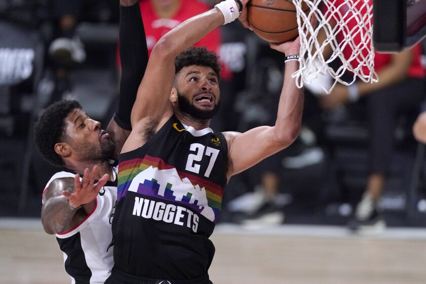 Nuggets guard Jamal Murray goes up for a shot as Clippers forward Paul George defends during Game 6 on Sunday.