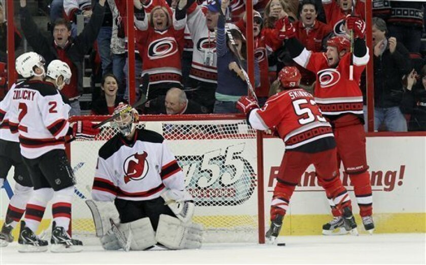 Carolina Hurricanes' Jordan Staal, right, and Jeff Skinner, second from right, celebrate a goal by teammate Jay Harrison against New Jersey Devils' goalie Johan Hedberg, of Sweden, during the first period of an NHL hockey game in Raleigh, N.C., Saturday, March 9, 2013. (AP Photo/Ted Richardson)