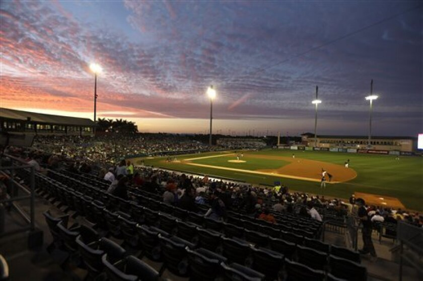 Baseball fans watch as the Miami Marlins play the Atlanta Braves during an exhibition spring training baseball game at Roger Dean Stadium Wednesday, March 13, 2013, in Jupiter, Fla. (AP Photo/Jeff Roberson)