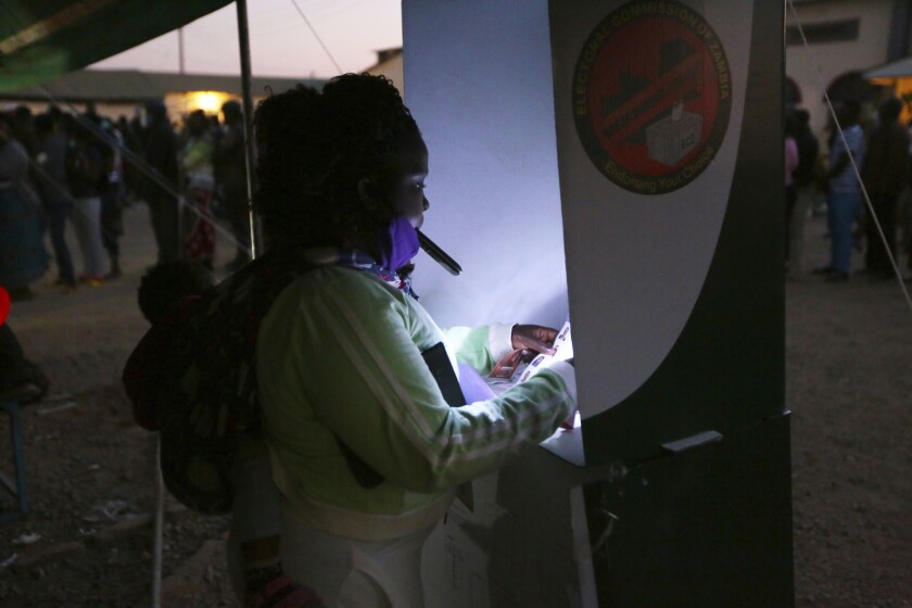 A woman uses her mobile phone to light the ballot box as she casts her vote at a polling station in Lusaka, Zambia, Thursday Aug, 12, 2021. Zambias standing as one of Africa's most stable democracies is being tested as the country votes amid violence, alleged intimidation and fears of vote rigging. (AP Photo/Tsvangirayi Mukwazhi)