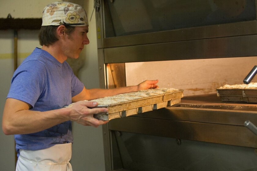 At the Prager Brothers Artisan Breads in Carlsbad, Clinton Prager loads the oven with baking pans filled with dough for spelt loaves of bread.