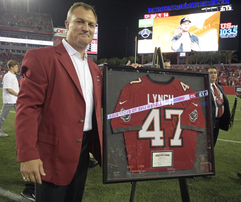 Former Bucs safety John Lynch poses with his jersey during a ceremony inducting him in the team's Ring of Honor in 2016.