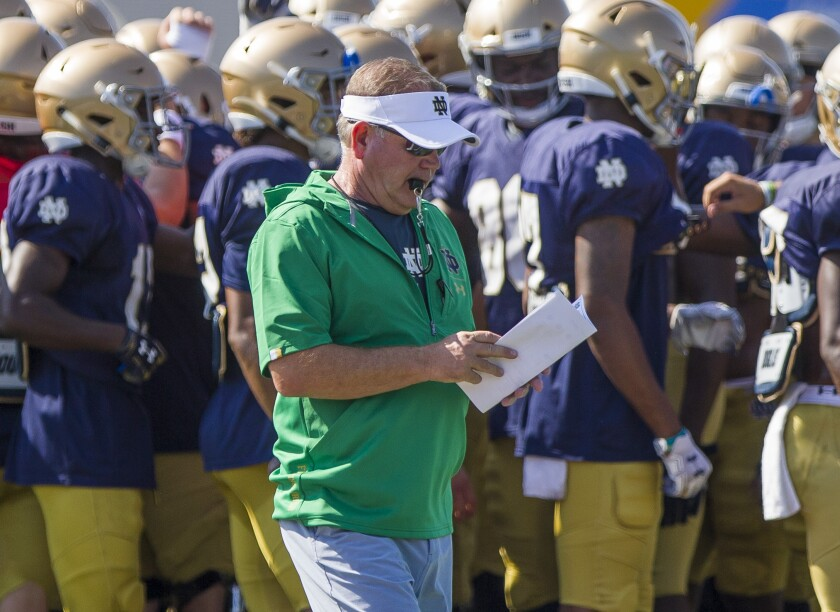 Notre Dame coach Brian Kelly looks at notes during a team practice session on August 8.