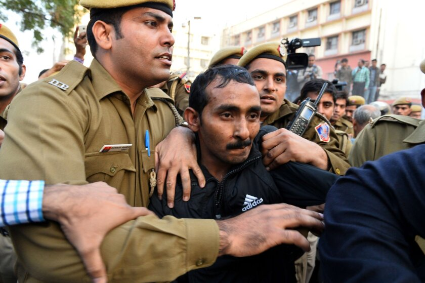 Shiv Kumar Yadav is escorted by police after a court appearance in New Delhi on Dec. 8, 2014.