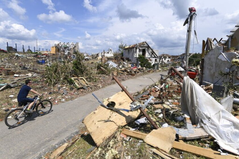 Man rides his bike after a tornado hit the village of Mikulcice in the Hodonin district, South Moravia, Czech Republic, Friday, June 25, 2021. A rare tornado tore through southeastern Czech Republic, killing a few people and injuring hundreds, rescue services said on Friday. (Ondrej Deml/CTK via AP)