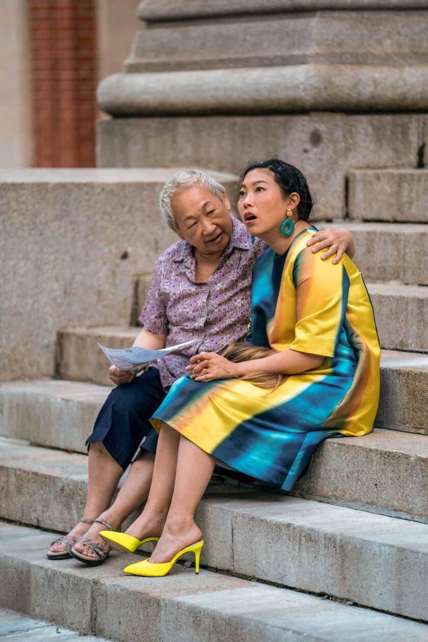 "Awkwafina, right, and Lori Tan Chinn, as her grandmother, sitting on steps in a scene from ""Awkwafina Is Nora From Queens."""