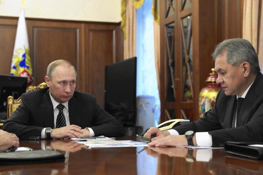 Russian President Vladimir Putin (left) listens to Defense Minister Sergei Shoigu in Moscow on Dec. 29, 2016, on the eve of a cease-fire in Syria brokered by Russia and Turkey.