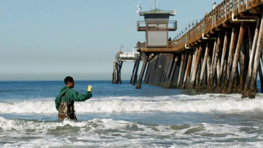Mar Vista High School sophomore Anthony Gass collects a water sample at the Imperial Beach Pier. The school and the Surfrider Foundation have teamed up to monitor water pollution north of Tijuana.