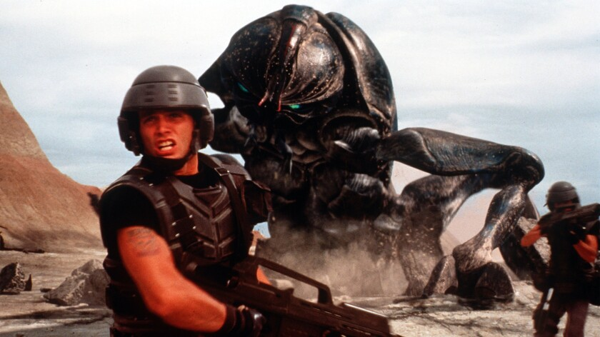 Soldiers battle monstrous bugs on a distant planet