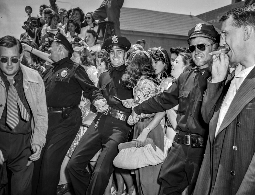 Aug. 11, 1943: Surging fans, held back by police, wait to see Frank Sinatra.