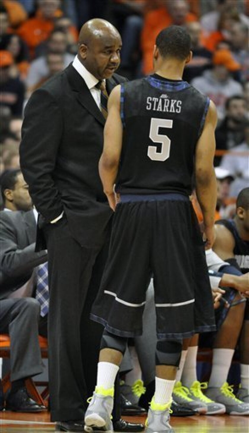 Georgetown head coach John Thompson III, left, talks with Markel Starks during the first half of an NCAA college basketball game against Syracuse in Syracuse, N.Y., Wednesday, Feb. 8, 2012. (AP Photo/Kevin Rivoli)