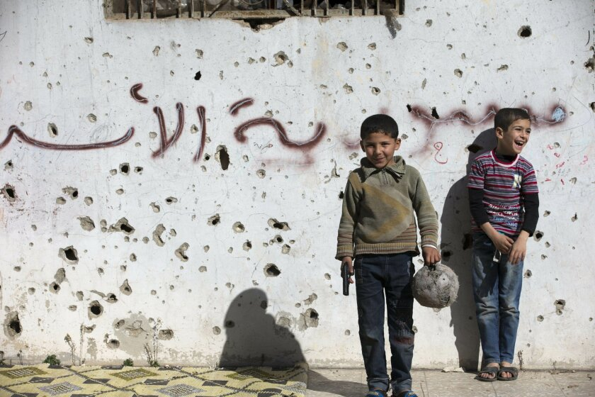 """A Syrian boy holds a toy gun as he plays soccer with others between destroyed buildings with graffiti that reads """"Syria al-Assad,"""" in the old city of Homs, Syria, Friday, Feb. 26, 2016. The U.N. Security Council is expected to vote Friday afternoon on a draft resolution endorsing the """"cessation of hostilities"""" in Syria that is set to start at midnight local time. The draft, obtained by The Associated Press, also urges the U.N. secretary-general to resume Syria peace talks """"as soon as possible.""""(AP Photo/Hassan Ammar)"""