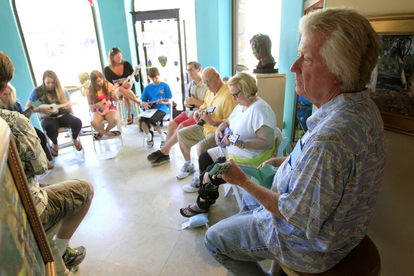 Dean Torrence, right, plays along during a Strummers of Surf City ukulele class.