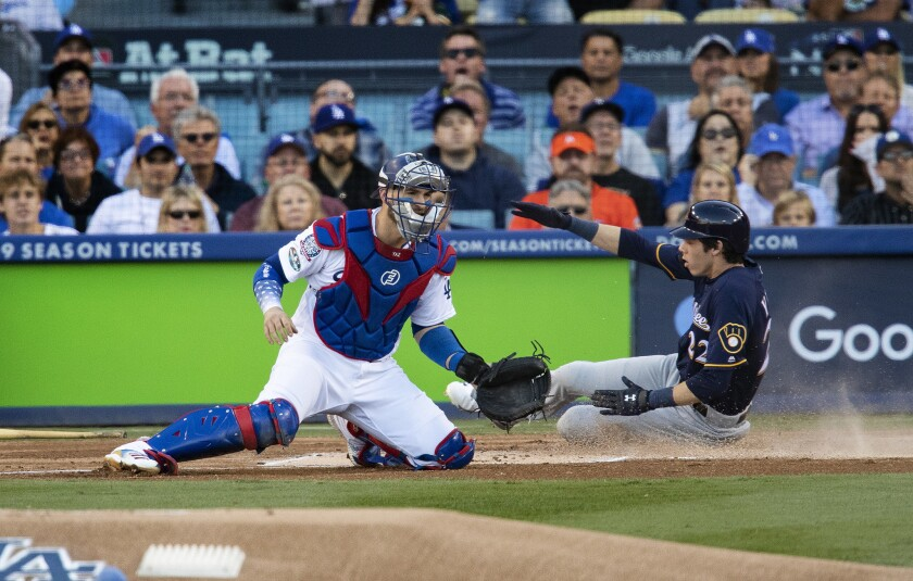 Milwaukee Brewers right fielder Christian Yelich slides past Dodgers catcher Yasmani Grandal to score the first run of the game on a double by Ryan Braun in the first inning of NLCS Game 3.