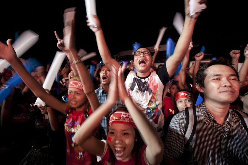 Supporters of Myanmar opposition leader Aung San Suu Kyi's National League for Democracy party cheer as they watch the results of the general election on an LED screen displayed outside the party's headquarters Monday, Nov. 9 2015 in Yangon, Myanmar. Myanmar voted Sunday in historic elections that