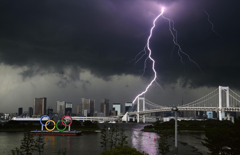 Lightning illuminates the sky over the Olympic rings and the Rainbow Bridge in Tokyo, Sunday, July 11, 2021. The opening ceremony of the postponed 2020 Summer Olympics is scheduled to be held in less than two weeks. (Kyodo News via AP)