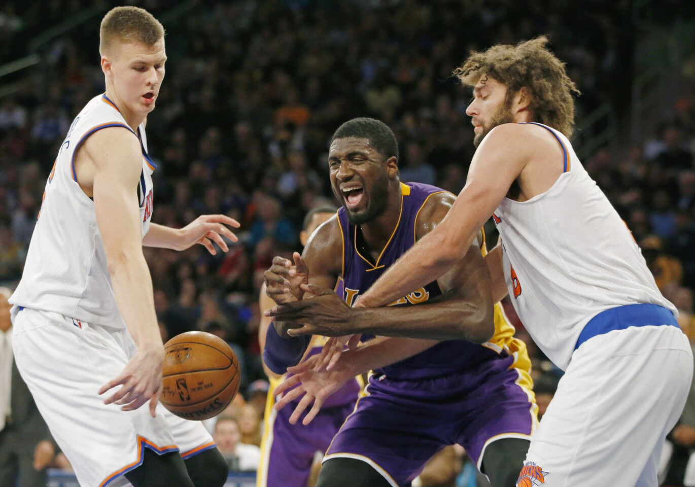 Lakers center Roy Hibbert loses control of the ball as he's defended by Knicks forward Kristaps Porzingis, left, and center Robin Lopez in the second half Sunday.