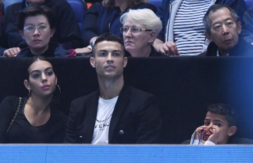 El futbolista portugués Cristiano Ronaldo (c) asiste junto a Georgina Rodríguez (i) y su hijo Cristiano Jr (d) al juego entre el tenista estadounidense John Isner y el serbio Novak Djokovic, el pasado 12 de noviembre. EFE/Archivo