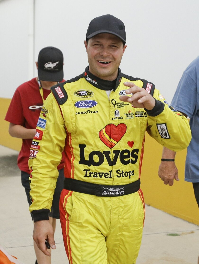 David Gilliland walks through the garage area after winning the pole position for the NASCAR Sprint Cup Series auto race at Daytona International Speedway in Daytona Beach, Fla., Friday, July 4, 2014. Qualifying was shortened due to rain. (AP Photo/John Raoux)