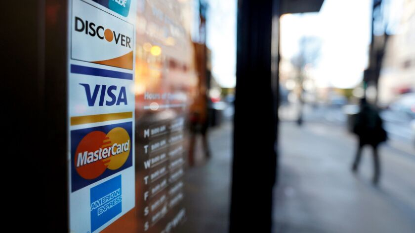 FILE- In this Jan. 31, 2018, file photo, credit card logos are posted to the door of a business in A