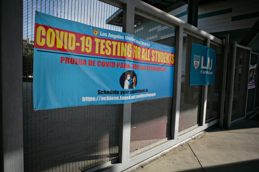 A blue banner offering COVID-19 tests is attached to a fence