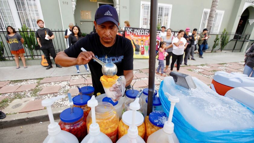 Street cart vendor Alex Ramirez serves up ice and fruit in Hollywood, close to the area where his s
