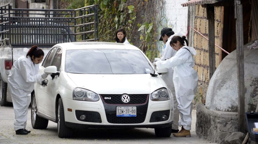 Forensic investigators inspect a car outside the home where Gisela Mota was killed, one day after ta