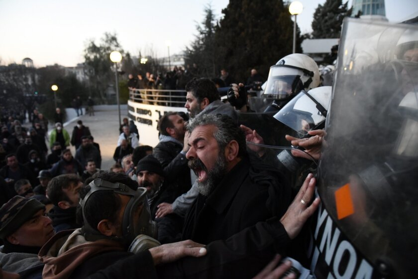 Protesting farmers scuffle with riot police officers during a rally in the northern Greek city of Thessaloniki on Thursday, Jan. 28, 2016. Greek farmers, protesting against the left-wing government's planned pension reforms, have clashed with riot police outside an agricultural fair in Thessaloniki. About 5,000 farmers took part in Thursday's protest, using 100 tractors to block access to the fair in the city center. (AP Photo/Giannis Papanikos)