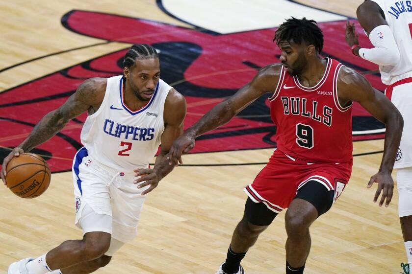 Kawhi Leonard, de los Clippers de Los Ángeles, dribla a Patrick Williams, de los Bulls de Chicago, en el duelo del viernes 12 de febrero de 2021 (AP Foto/Nam Y. Huh)
