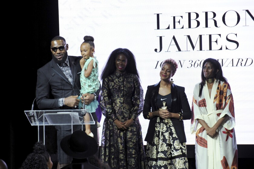 Lakers star LeBron James holds his daughter Zhuri as he accepts the Harlem Fashion Row's ICON 360 Award on Sept. 4.