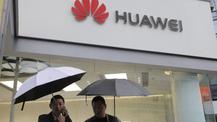 FILE - In this Thursday, March 7, 2019 file photo, two men use their mobile phones outside a Huawei