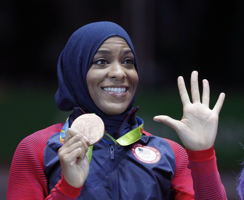 American athlete Ibtihaj Muhammad poses with her bronze medal after the women's team sabre fencing competition at the 2016 Summer Olympics in Rio de Janeiro.