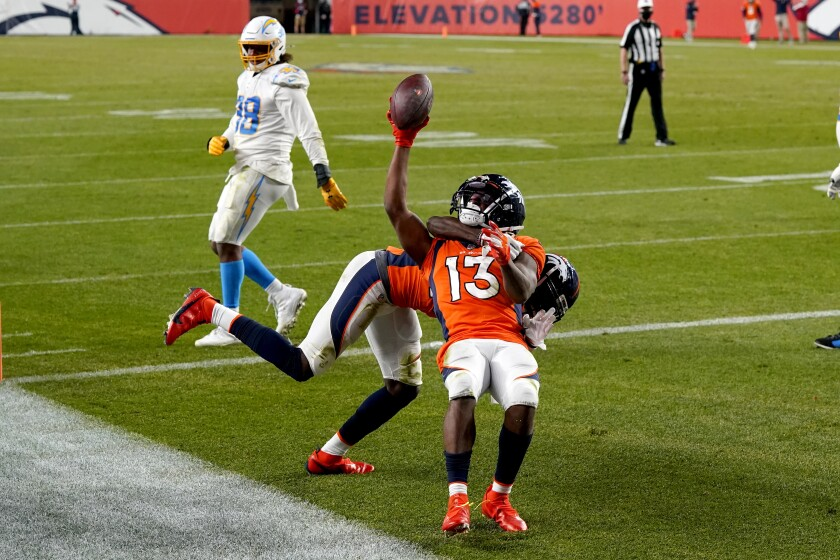 Denver Broncos' K.J. Hamler is pulled to the ground by a teammate as they celebrate Hamler's touchdown against the Chargers