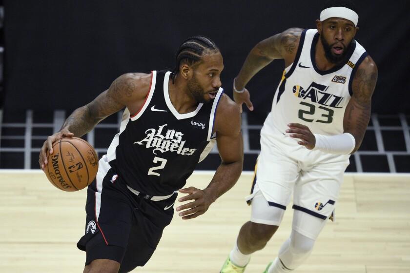 Los Angeles Clippers forward Kawhi Leonard is defended by Utah Jazz forward Royce O'Neale.