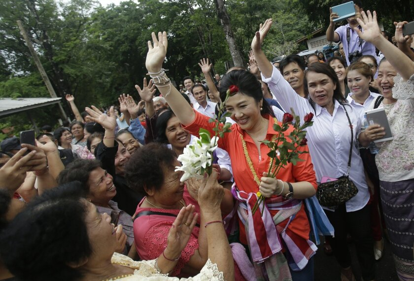 In this May 30, 2016 photo, Thailand's former prime minister Yingluck Shinawatra meets with fans in Bueng Kan Province, Thailand. As the former prime minister made her way through a line of fans, some cried, others screamed and a few embraced her. This was not a political campaign stop. If it had b