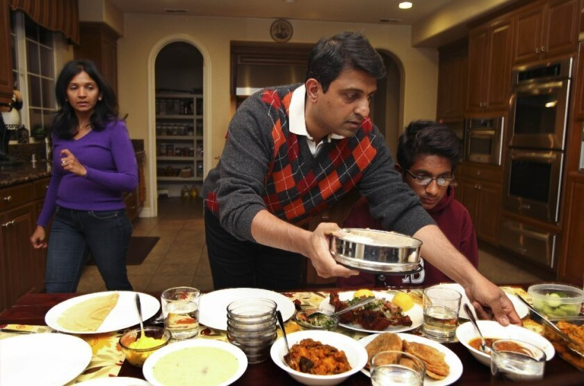 Dr. Harish Hosalkar helps serve the dinner that he just cooked for his family at their home in Scripps Ranch. With him are his wife, Dr. Hetal Hossalkar, and their son Hriday. / photo by Hayne Palmour IV * U-T