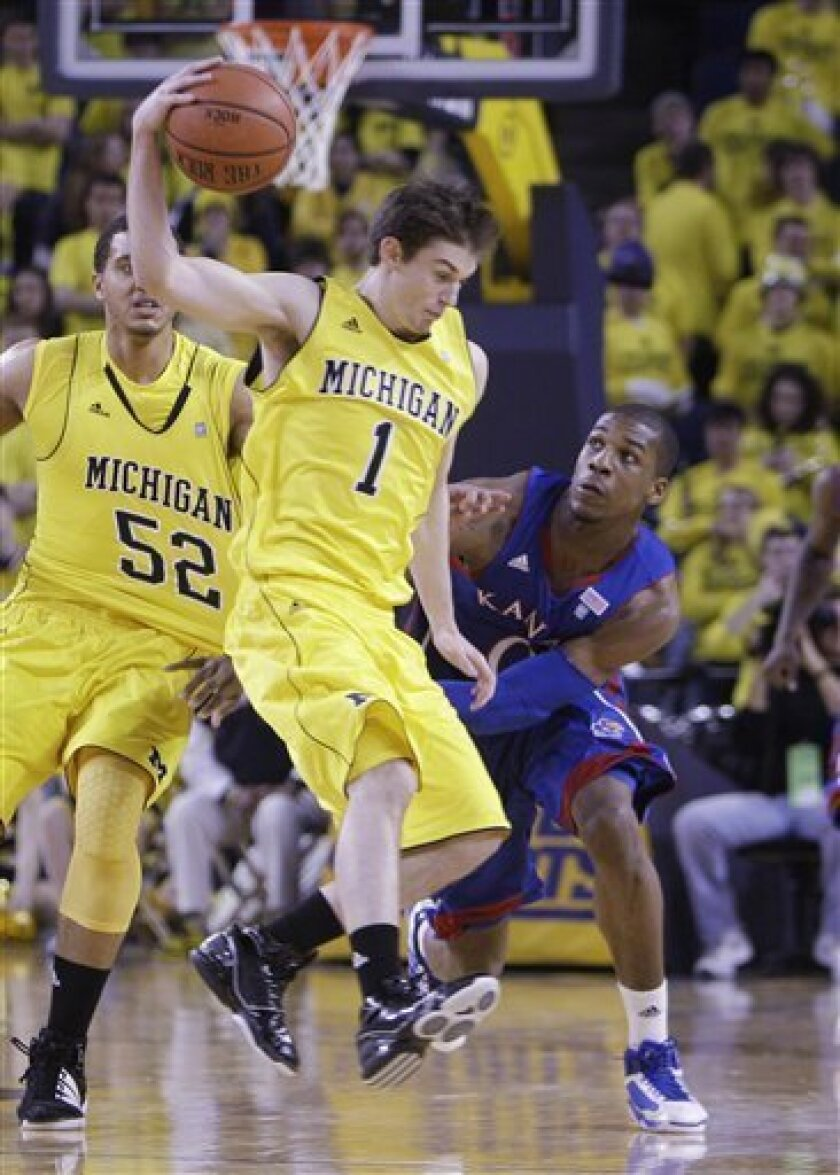Kansas forward Thomas Robinson looks on as Michigan guard Stu Douglass (1) controls the ball during the first half of an NCAA college basketball game in Ann Arbor, Mich., Sunday, Jan. 9, 2011. (AP Photo/Carlos Osorio)