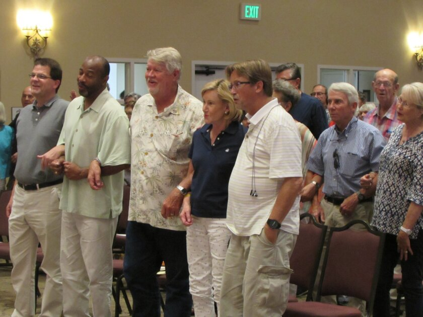 (From left) Pastors Paul Cunningham and Charles Norris join guests — locking arms and voices.