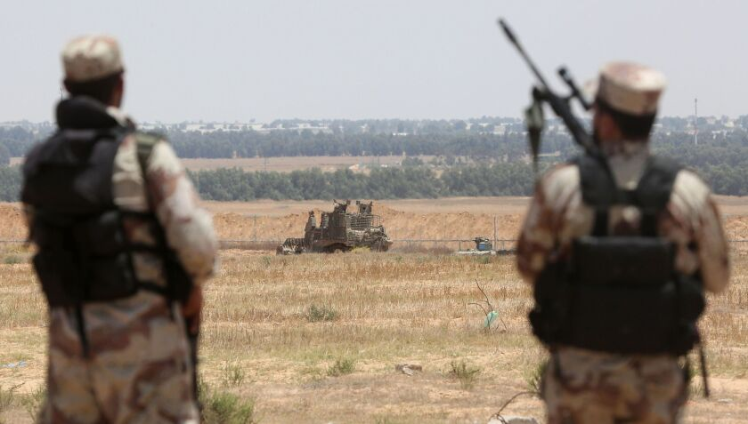 Palestinian militants of the Izzidin al-Qassam Brigade watch an Israeli bulldozer working along a fence that separates the southern Gaza Strip and Israel on June 3. Rocket fire into Israel later in the day was followed by Israeli airstrikes June 4 on Gaza.