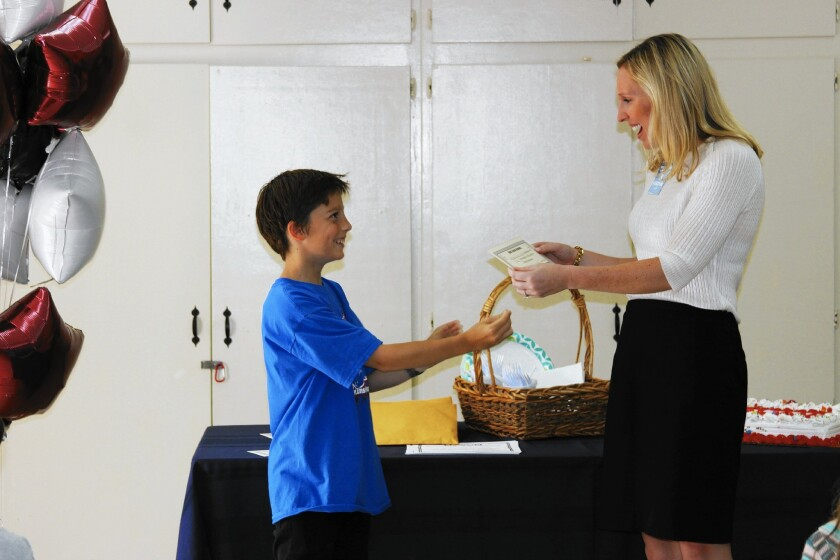 Jackson Ellsworth, a fifth-grader at the Albert Einstein Academy in Huntington Beach, presents a $115 donation to Carley Prendergast of the Hoag Hospital Foundation after Jackson's team, Bracelets for Friends, made and sold bracelets as a class project and chose the foundation as its beneficiary.