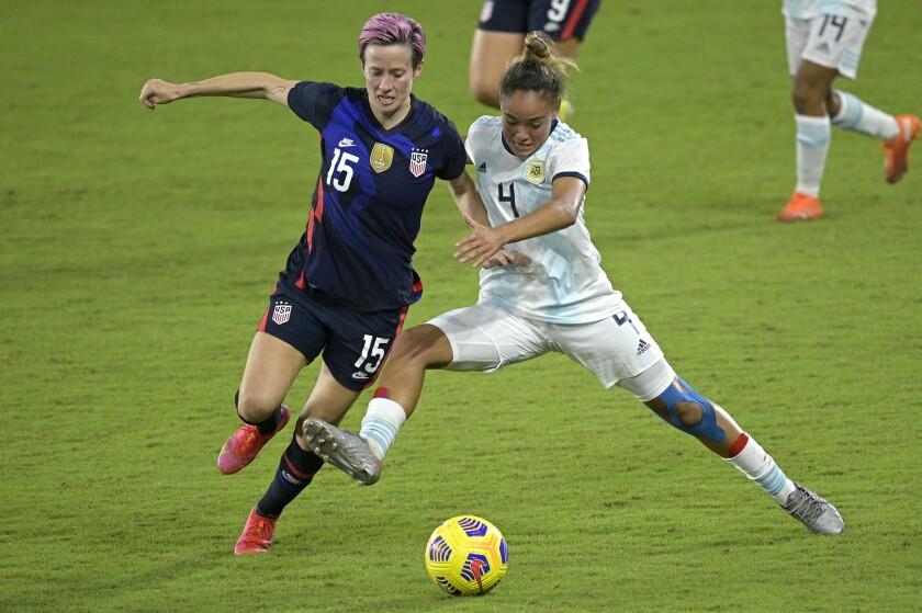 U.S. forward Megan Rapinoe and Argentina defender Marina Delgado compete for the ball.