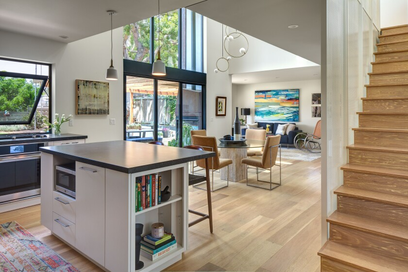 A remodeled main living area is modern and open, with hardwood floors and lots of natural light from large windows.