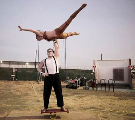 Matt Allmen holds up his fellow performer Elisabeth Carpenter as they rehearse their routine outside the big tent shortly before Cirque Berzerk show time July 23.