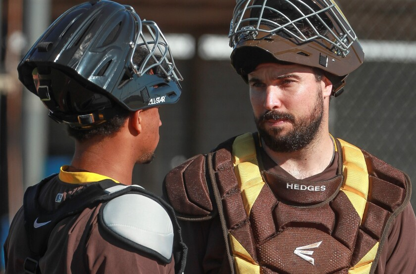 Padres catchers Austin Hedges, right, and Francisco Mejia talk during spring training at the Peoria Sports Complex.