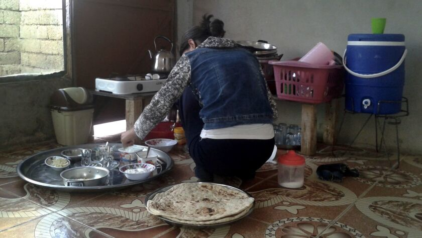 Seve's daughter-in-law, Amira, makes breakfast at the sparsely furnished house that was loaned to th