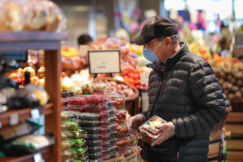 Conrad Kellenberger of North Park, wearing a face mask, shops in the Barons Market, North Park location, during the seniors-only time, one hour before the store opened to the general public, March 20, 2020 in San Diego, California. The seniors-only shopping is one of the many byproducts of the coronavirus outbreak, because older adults are one of the most vulnerable groups along with people with underlying heath issues are more susceptible to the virus.