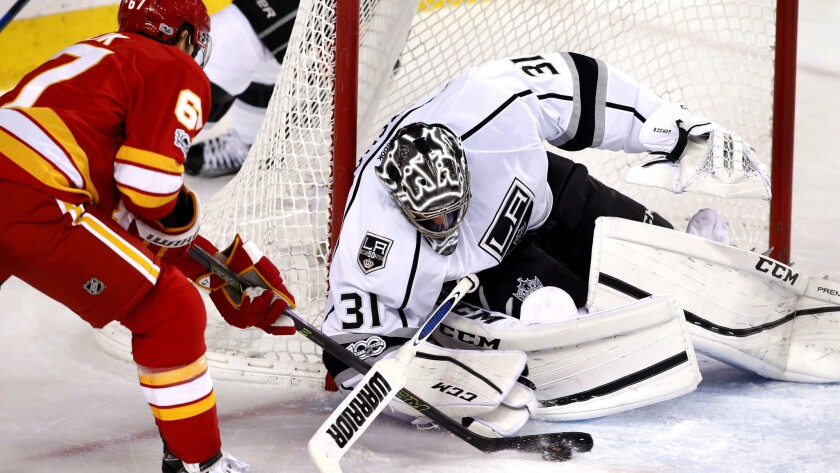 Kings goalie Ben Bishop tries to cover the puck while Flames right wing Michael Frolik tries to control the rebound after save during the third period Wednesday night.