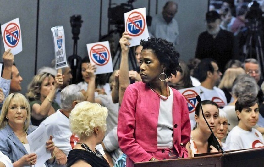 Opponents of proposed freeway alternatives for the San Gabriel Valley hold up their signs as Michelle Smith, project manager of the Metropolitan Transportation Authority, stands at the podium.